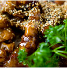 Sesame Beef Lightly breaded flank steak strips sautéed with spicy garlic flavored sweet sauce, topped with sesame seeds, and served on a bed of Chinese vermicelli noodles.